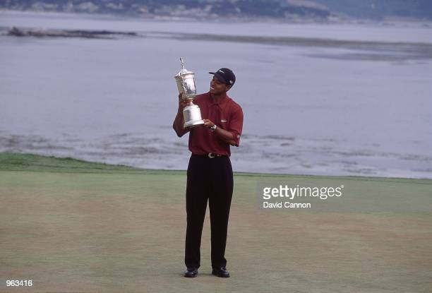 Tiger Woods of the USA poses with the winning trophy after winning the 100th US Open held at the Pebble Beach Golf Links in Pebble Beach California...