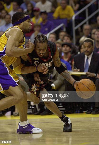 Allen Iverson of the Philadelphia 76ers dribbles around Derek Fisher of the Los Angeles Lakers during Game 1 of the NBA Finals at Staples Center in...
