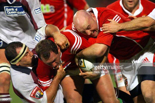 Flanker Richard Hill and hooker Keith Wood of the British Lions combine to drive against hooker Michael Foley of the Queensland Reds during the match...