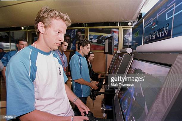 Jenson Button of Great Britain and Giancarlo Fisichella of Italy and Benetton play the new Playstation 2 Formula One game in the paddock during the...