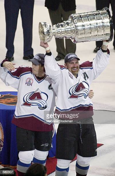 Joe Sakic and Ray Borque of the Colorado Avalanche hold up the Stanley Cup after defeating the New Jersey Devils in game seven of the NHL Stanley Cup...
