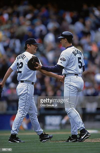 Kazuhiro Sasaki of the Seattle Mariners shakes the hand of teammate John Olerud during the game against the Tampa Bay Devil Rays at Safeco Field in...
