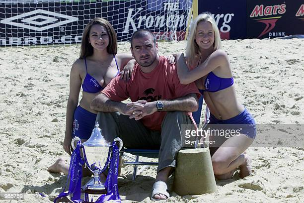 Kronenbourg promotional girls pose with ex Manchester United player Eric Cantona for photographers during the Kronenbourg Beach Soccer Cup played at...