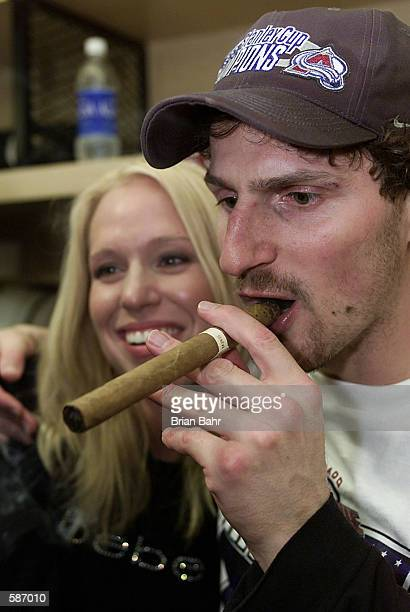 Milan Hejduk of the Colorado Avalanche lights up a stogie with his wife at his side after Game 7 of the Stanley Cup Finals at the Pepsi Center in...