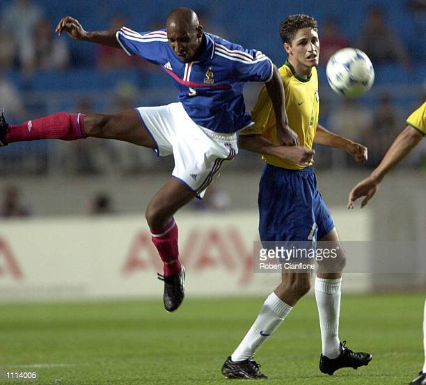 Nicolas Anelka of France is challenged by Edmilson of Brazil during the 2001 FIFA Confederations Cup semi final between France and Brazil played at...