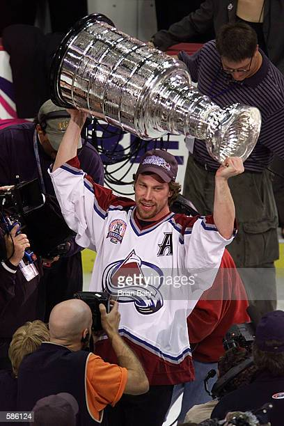 Peter Forsberg of the Colorado Avalanche raises the Stanley Cup in Denver, Coloardo after losing his spleen earlier, during the Western Conference...