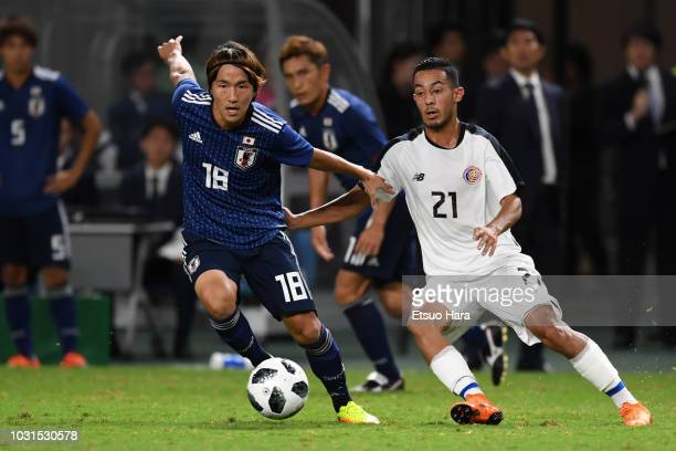 Jun Amano of Japan and Jimmy Marin of Costa Rica compete for the ball during the international friendly match between Japan and Costa Rica at Suita...