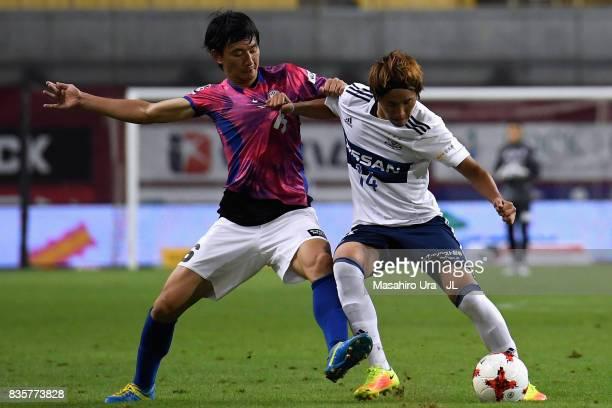 Jun Amano of Yokohama F.Marinos controls the ball under pressure of Hideto Takahashi of Vissel Kobe during the J.League match between Vissel Kobe and...