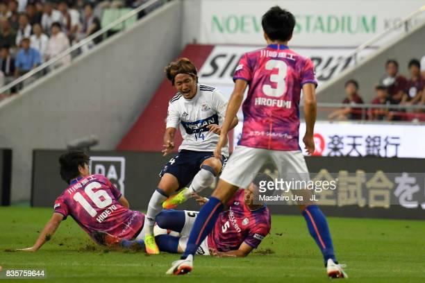 Jun Amano of Yokohama F.Marinos is challenged by Hideto Takahashi and Takuya Iwanami of Vissel Kobe during the J.League match between Vissel Kobe and...