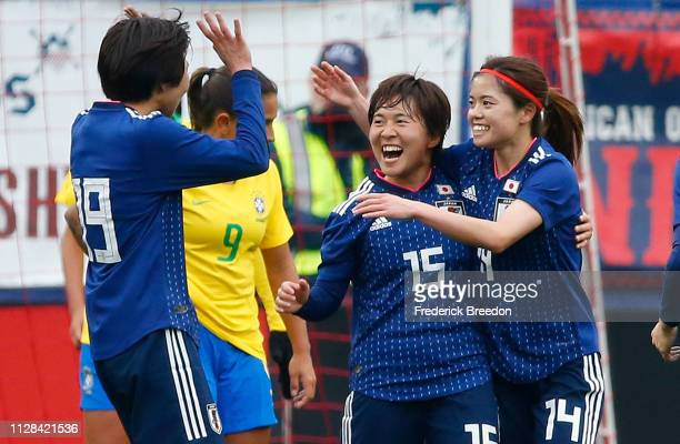 Jun Endo and Uuka Momiki of Japan congratulate teammate Yui Hasegawa on scoring a goal against Brazil during the second half during the 2019...