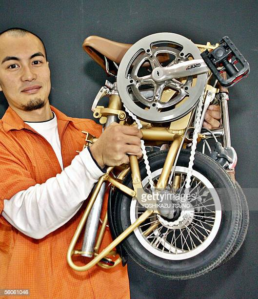 Jun Ichikawa an employee with Japanese cycle maker Pearl Metal known as the Captainstag brand displays a prototype model of a foldable bicycle called...