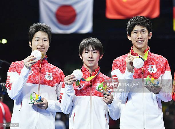 Jun Mizutani, Koki Niwa and Maharu Yoshimura of Japan hold up their silver medals during the award ceremony for the men's table tennis team event at...