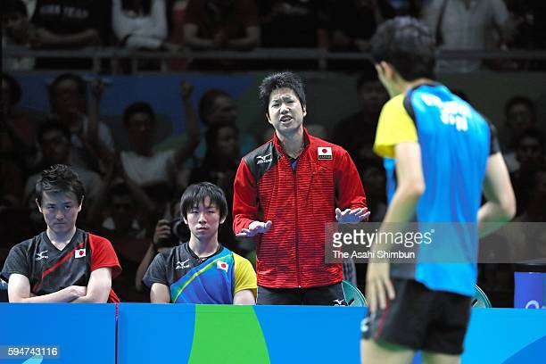 Jun Mizutani of Japan gestures to Maharu Yoshimura competing against Ma Long of China in the Men's Team Table Tennis gold medal match on Day 12 of...