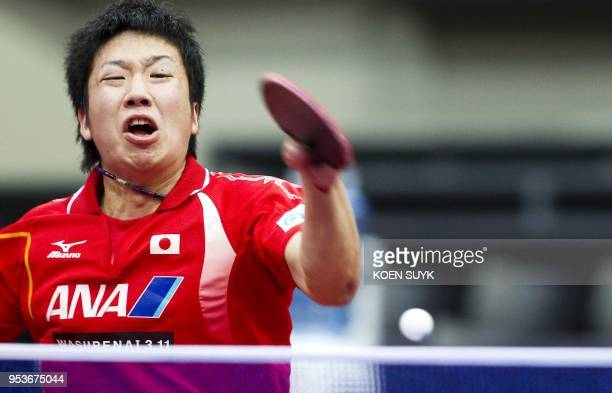 Jun Mizutani of Japan returns against Adrien Mattenet of France during their men's singles fourth round match at the table tennis world championship...