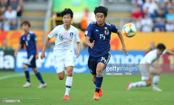 Jun Nishikawa of Japan is chased by Hojin Jeong of Korea Republic during the 2019 FIFA U20 World Cup Round of 16 match between Japan and Korea...