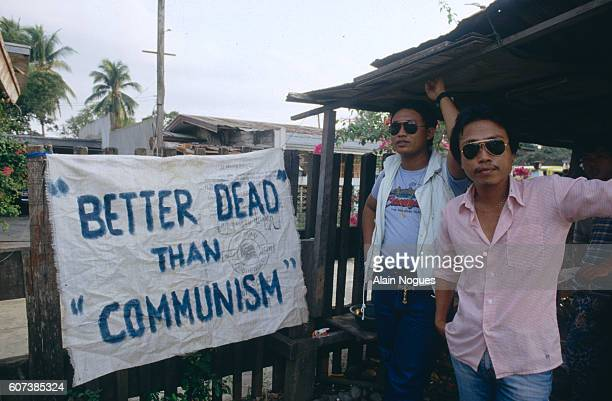 Jun Pala's bodyguards next to an antiCommunist sign in a battle against the guerrilleros of the New People's Army the fighting wing of the Communists