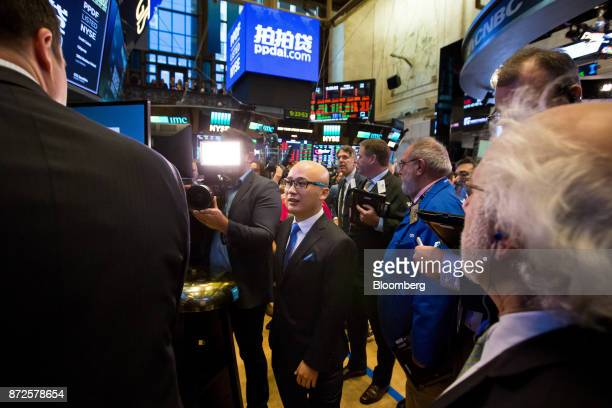 Jun Zhang chief executive officer and founder of PPDAI Group Inc center speaks with traders during the company's initial public offering on the floor...