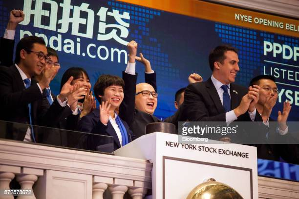 Jun Zhang chief executive officer and founder of PPDAI Group Inc center rings the opening bell during the company's initial public offering on the...