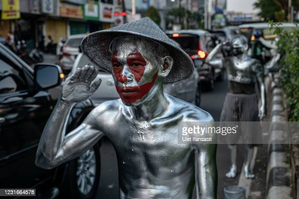 Junaidi , wearing silver paint begs for money on the street, was an employee at a company, but due to the pandemic he was laid off and become a...