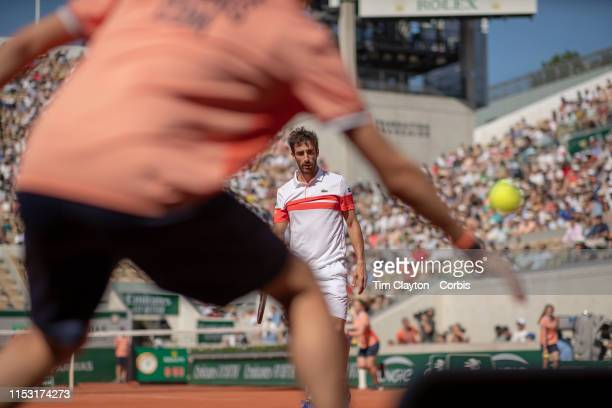 June 01 Pablo Cuevas of Uruguay in is passed by Dominic Thiem of Austria as the Baal boy reaches for the ball during the Men's Singles third round...
