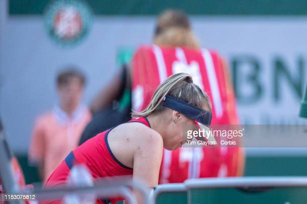 June 01 Sofia Kenin of the United States sobs in her chair after beating Serena Williams of the United States who leaves the court in the background...