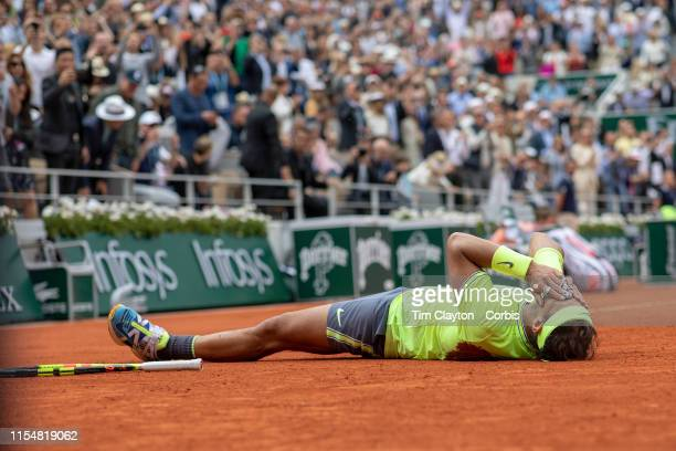 June 09. Rafael Nadal of Spain lies on the clay court as he celebrates winning his twelfth French Open title after his victory against Dominic Thiem...