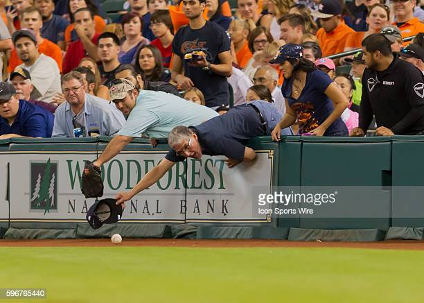 Fans attempt to harvest a foul ball during the MLB game between the Seattle Mariners and the Houston Astros as Minute Maid Park in Houston TX