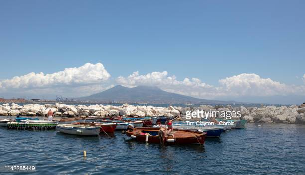 Local enjoy sunbathing and a swim on the shore front of Naples showing the Gulf of Naples in Campania with the volcano Mount Vesuvius providing a...