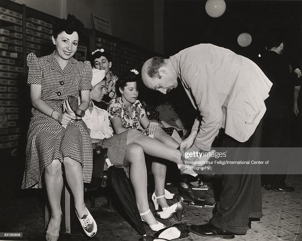 With the all important No. 17 coupon expiring Tuesday, New York shoe stores were jammed even on Sunday. These young ladies are trying on some white models at a store on Delancey St., on lower East Side, New York, 1943. (Photo by Weegee (Arthur Fellig)/International Center of Photography/Getty Images)