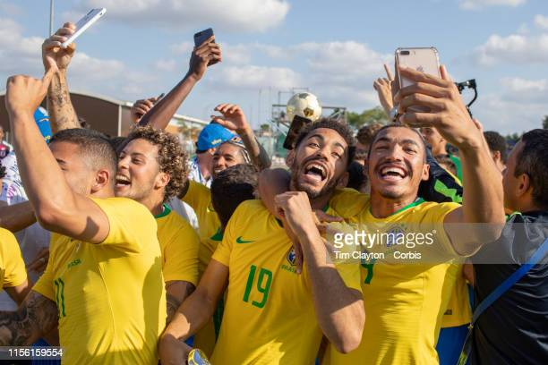 June 15 Matheus Cunha of Brazil and Adryelson of Brazil celebrate after the trophy presentation and take images of themselves with their mobile...
