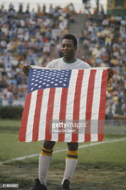 June 15th 1975, New York Cosmos' Pele holds an American flag on the field.