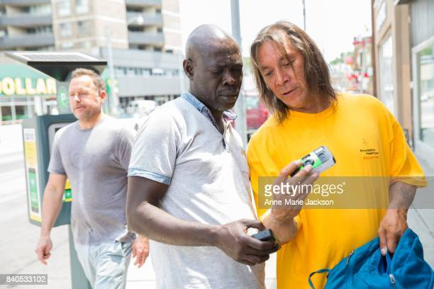 TORONTO ON June 17 2017 Kenneth and Ray check their cameras before taking part in My Toronto an initiative that engages people who experience...