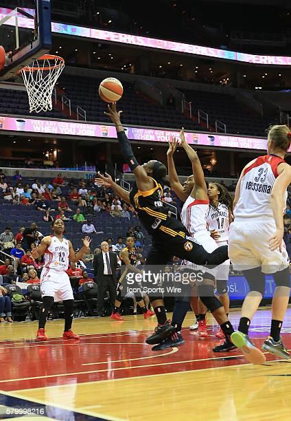 Karima Christmas of the Tulsa Shock shoots as Armintie Herrington of the Washington Mystics moves in during a WNBA game at Verizon Center in...