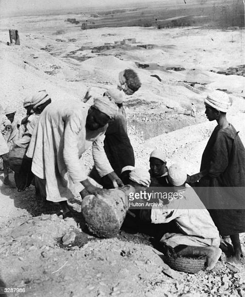 Porters or diggers with pots at the Luxor excavation sponsored by George Carnarvon and part of a set of sepia photographs