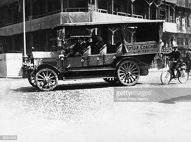 A motor coach takes people to see the stands set up in preparation for the coronation of George V and a cyclist tags along for a free ride