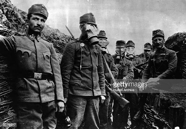 Austrian soldiers in the trenches demonstrating their gas masks