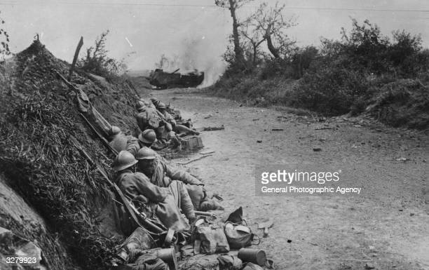 French soldiers taking cover in a road near Courcelles France whilst a tank is hit by a German shell