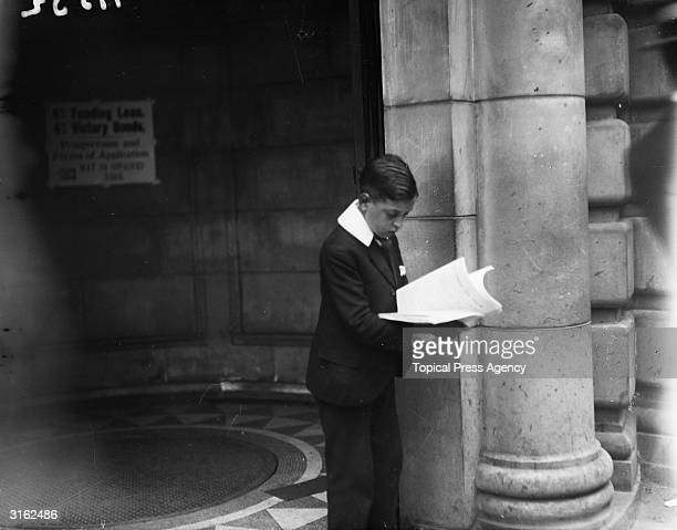 An office boy reading a prospectus for the 'Peace And Joy' victory loan scheme launched in London