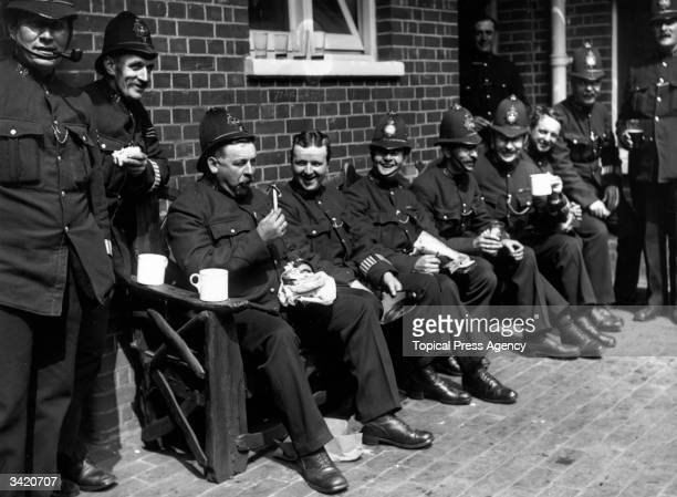 Police officers sit on a bench outdoors enjoying their lunch