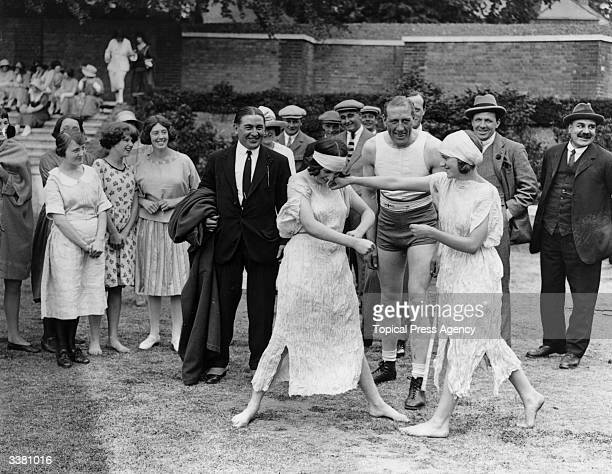 A crowd of onlookers including English boxer Bombardier Billy Wells watching two women boxing at a garden fete in Hampstead north London