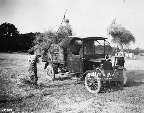 Farmworkers loading hay on to a Model 'T' Ford truck at a farm in Bedford England