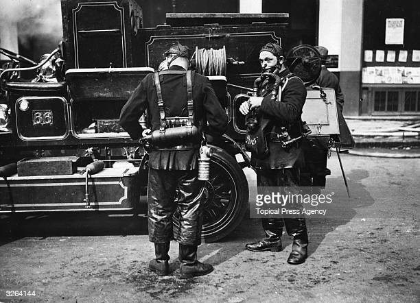 Firemen fixing on their smoke helmets as the Dominion rubber works burns in Farringdon Street