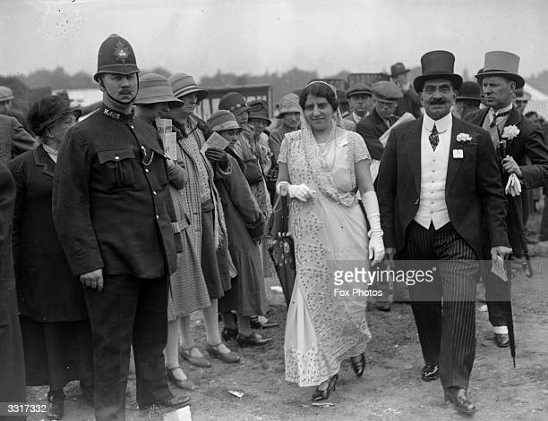 A couple of Ascot racegoers all dressed up for the occasion are under the critical eye of the crowd and a bored policeman