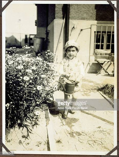 EXCLUSIVE A fulllength portrait of Margot Frank the older sister of Anne Frank holding a watering pitcher next to flowers in a garden Frankfurt am...