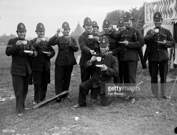 Policemen enjoying a cup of tea whilst on duty at Epsom Downs on Derby day