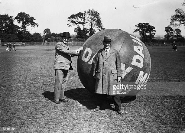 Two men standing in front of a huge ball inscribed with the words 'Daily Mail' at the opening of a new sports ground in Tottenham London