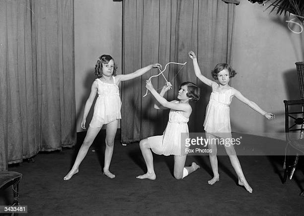 From left to right Felicity Fenella and Veronica Harrison pose in classical costumes with a Cupid's bow