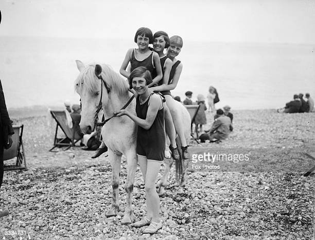 Girls riding a pony on the beach at Hastings
