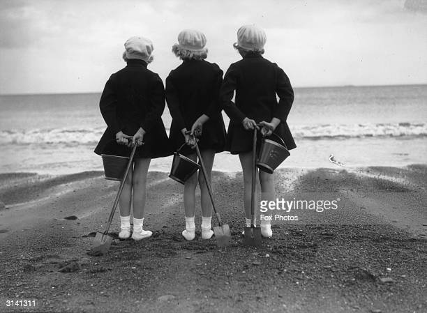 Wearing coats and berets against the chill of an English summer three children have brought their buckets and spades to the beach at Whitby in...