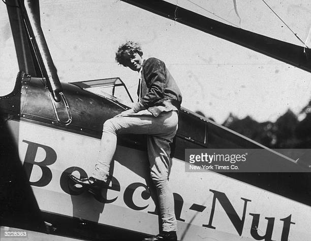 American aviator Amelia Earhart climbs into the cockpit of her airplane at Willow Grove Pennsylvania just before embarking on a trip to California